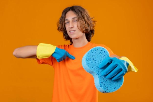 Joven en camiseta naranja con guantes de goma sosteniendo una esponja apuntando a sí mismo mirando confiado y satisfecho de pie sobre fondo amarillo