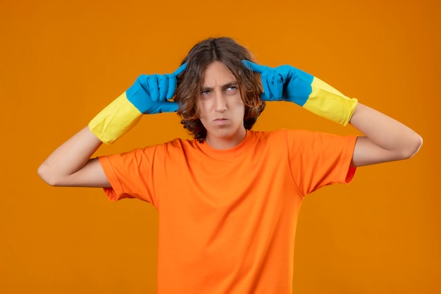 Joven en camiseta naranja con guantes de goma tocando las sienes se centró en la tarea de pie con cara seria sobre fondo amarillo