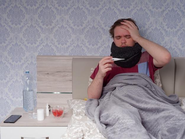 Un joven con una camiseta roja se sienta en la cama y mide su temperatura con un termómetro electrónico, el concepto de enfermedad en casa