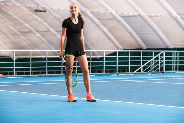 La joven en una cancha de tenis cerrada con pelota