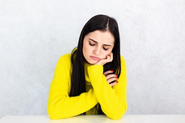 Joven cansada mujer sentada a la mesa en casa con dolor de cabeza