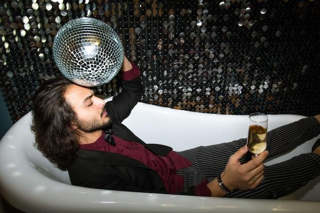 Joven cansado con bola de discoteca por cabeza y flauta de champán relajante en la bañera en la fiesta en el club nocturno