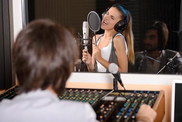Joven cantante femenina con técnico de estudio.