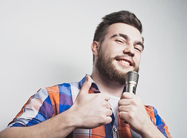 Joven cantante con micrófono sobre fondo gris