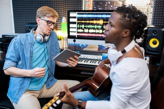 Joven cantante o músico de etnia africana tocando la guitarra y cantando mientras su colega graba la canción en el estudio