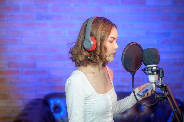 Una joven cantante sonriente con auriculares con micrófono mientras graba una canción en un estudio de música con luces de colores.