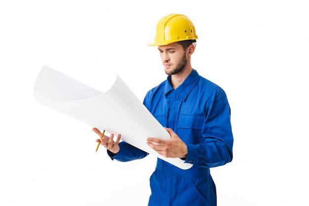 Joven capataz pensativo en uniforme azul y casco amarillo con plan de nuevo proyecto en manos