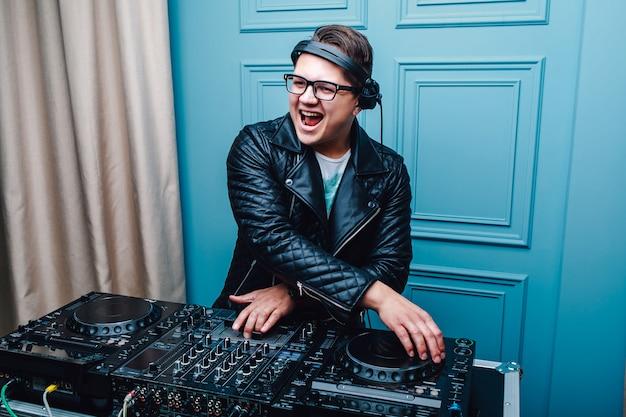 Joven carismática de dj con gafas y chaqueta de piel. cool dj en el trabajo.