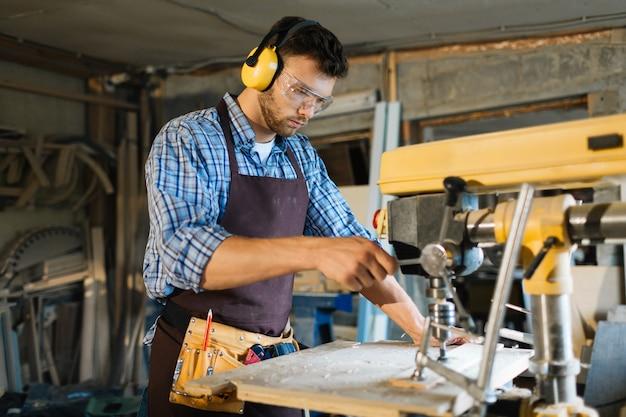 Joven carpintero enfocado en el trabajo