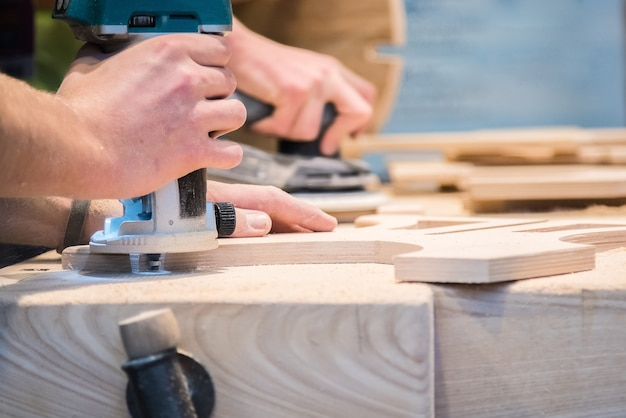 Joven carpintero pulido cortar decoración de madera con máquina de papel de lija eléctrica.
