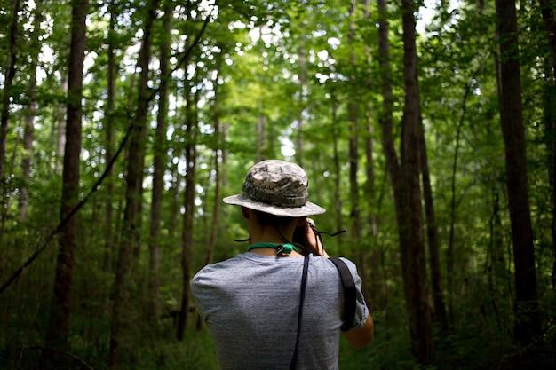 Joven casual con gorra verde en un parque de la selva hace fotos de la naturaleza