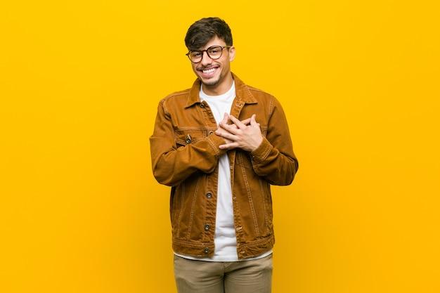 Joven casual hispano tiene expresión amistosa, presionando la palma contra el pecho. concepto de amor.