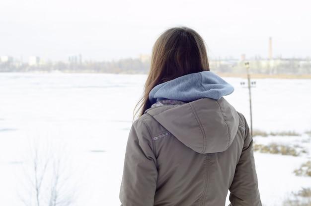 Una joven caucásica con un abrigo marrón.