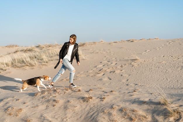 Joven caucásica en algún lugar con una chaqueta de cuero y pantalones de mezclilla corre a lo largo de la playa de arena con su perro beagle amistad entre un perro y un hombre. actividad de fin de semana emociones positivas