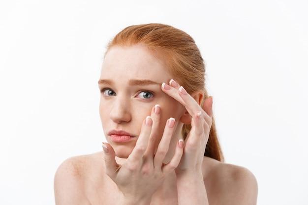 Joven caucásica aprieta el acné en la cara de la belleza