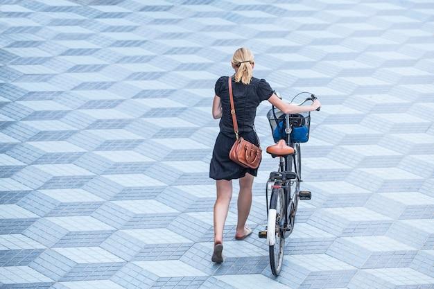 Joven caucásica con aspecto urbano camina con su bicicleta por una zona solitaria