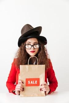 Joven caucásica concentrada con bolsa de compras