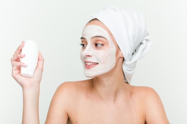 Joven caucásica disfrutando de un tratamiento de máscara facial con una botella de crema hidratante