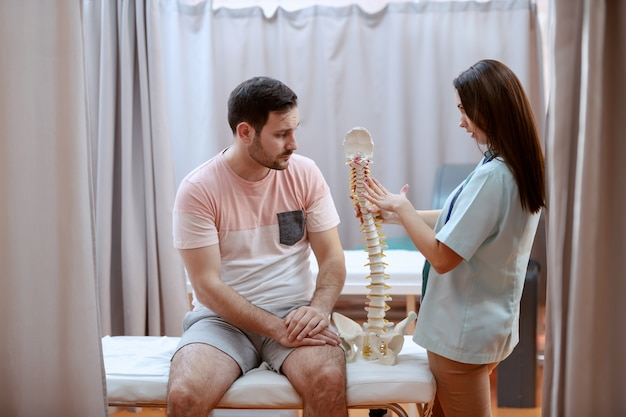 Joven caucásica doctora mostrando modelo de columna a su paciente masculino.
