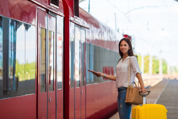 Joven caucásica con equipaje en la estación que viaja en tren