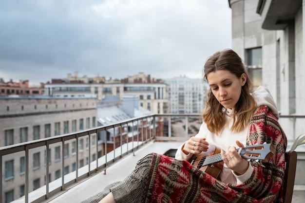 Joven caucásica hipster / hippie mujer en ropa casual tocando la guitarra hawaiana, canta una canción en un ukelele en la casa en la terraza.