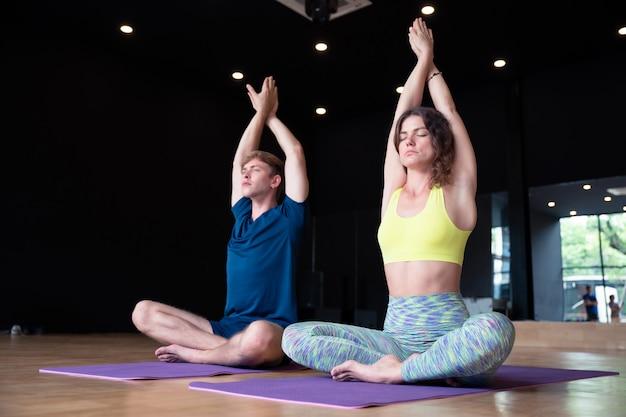 Joven caucásica hombre y mujer en sala de clase de yoga entrenamiento físico