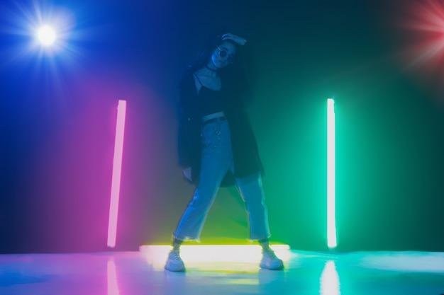 Joven caucásica posando con estilo en la sala de luz de neón