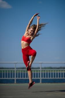 Joven caucásica en ropa deportiva bailando al aire libre