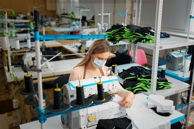 Joven caucásica sastre trabajando en fábrica de costura con máscara médica protectora