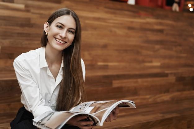 Joven caucásica sentada en las escaleras, leyendo una revista, sonriendo a la cámara.