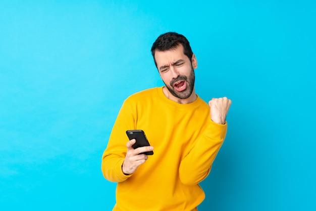 Joven caucásica sobre pared azul aislada con teléfono en posición de victoria