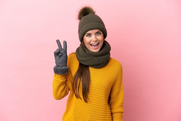 Joven caucásica con sombrero de invierno aislado sobre fondo rosa sonriendo y mostrando el signo de la victoria