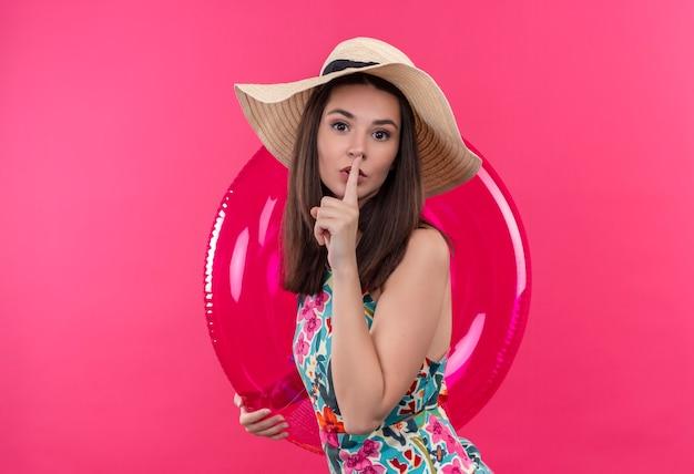 Joven caucásica con sombrero sosteniendo anillo de natación y sosteniendo el dedo sobre el labio gesticulando silencio sobre fondo rosa aislado