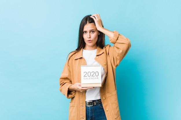 Joven caucásica sosteniendo un calendario de 2020 sorprendida, ha recordado una reunión importante.