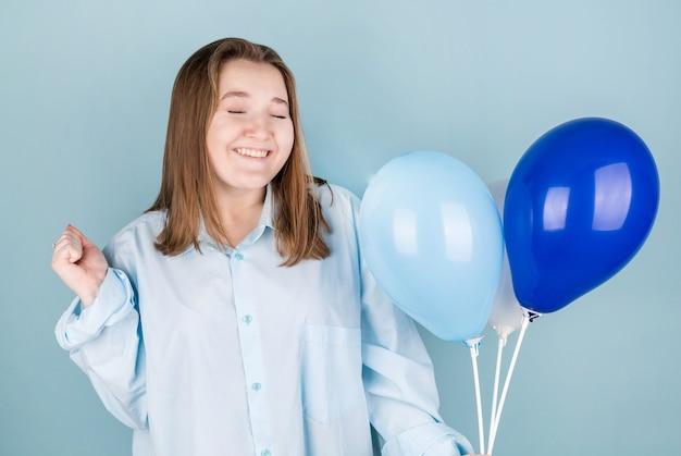 Joven caucásica sosteniendo globos con diferente expresión, sonriendo y cerrando los ojos. celebrando cumpleaños en azul