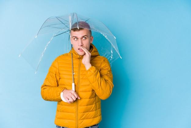 Joven caucásica sosteniendo un paraguas está diciendo una noticia secreta de frenado en caliente y mirando a un lado