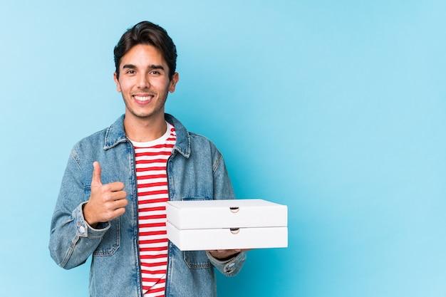 Joven caucásica sosteniendo pizzas aisladas sonriendo y levantando el pulgar hacia arriba