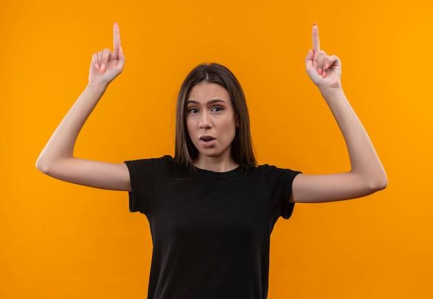 Joven caucásica vistiendo camiseta negra apunta hacia arriba con ambas manos en la pared naranja aislada