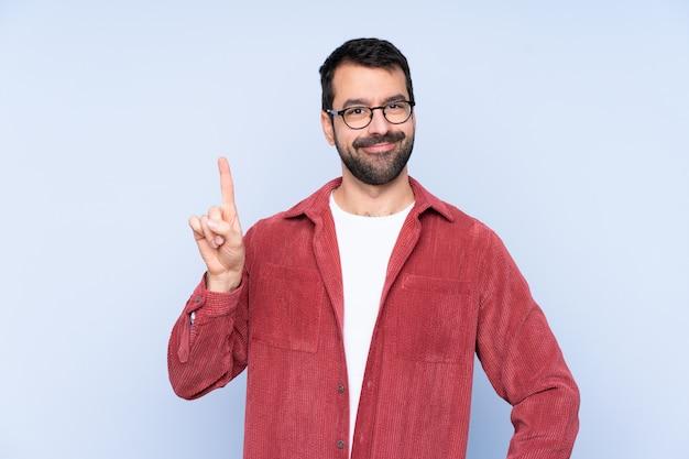 Joven caucásica vistiendo chaqueta de pana sobre pared azul mostrando y levantando un dedo en señal de lo mejor