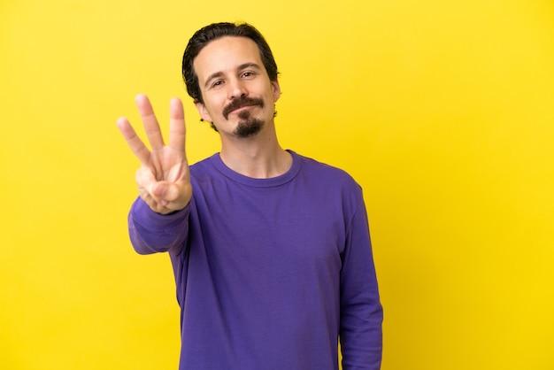 Joven caucásico aislado sobre fondo amarillo feliz y contando tres con los dedos