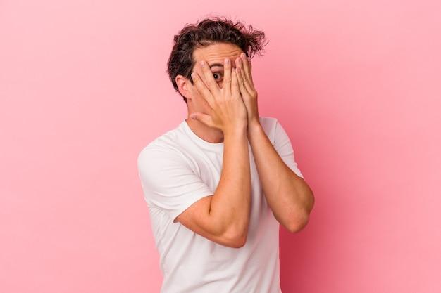 Joven caucásico aislado sobre fondo rosa parpadea a través de los dedos asustado y nervioso.