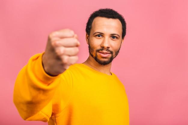 Joven caucásico aislado sobre rosa mostrando el puño a la cámara, expresión facial agresiva.