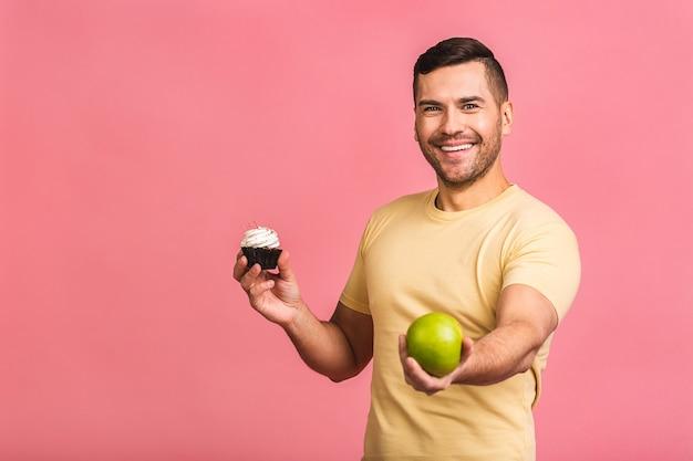 Joven caucásico alegre en casual hizo una elección equivocada al decidir entre pastel y manzana verde fresca