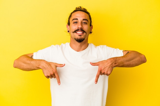 Joven caucásico con cabello largo aislado sobre fondo amarillo apunta hacia abajo con los dedos, sentimiento positivo.