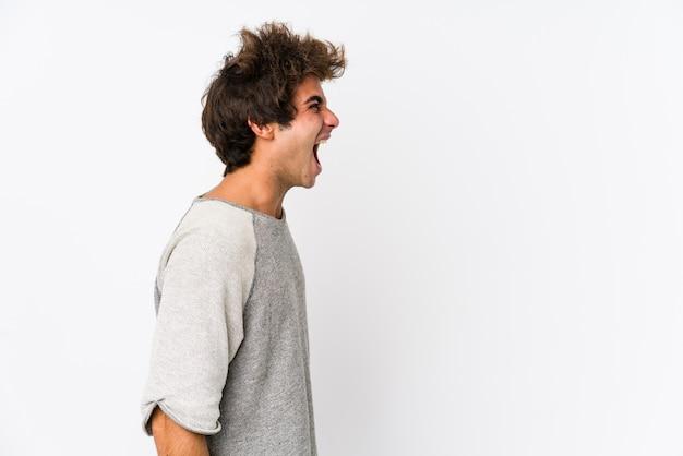 Joven caucásico contra una pared blanca gritando hacia un espacio en blanco