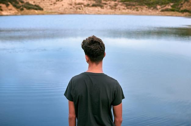 Joven caucásico disfrutando de la vista al lago