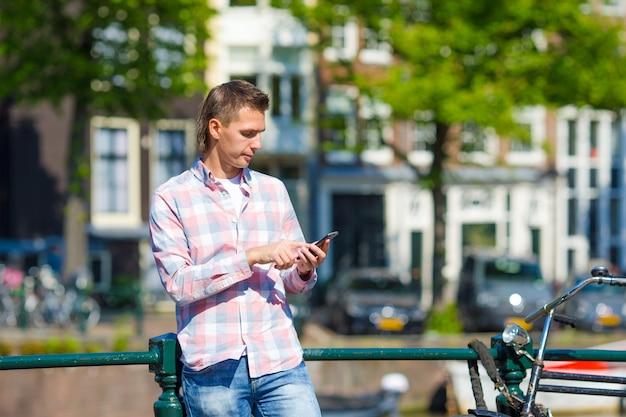 Joven caucásico escribiendo mensajes por teléfono al aire libre en ciudad europea