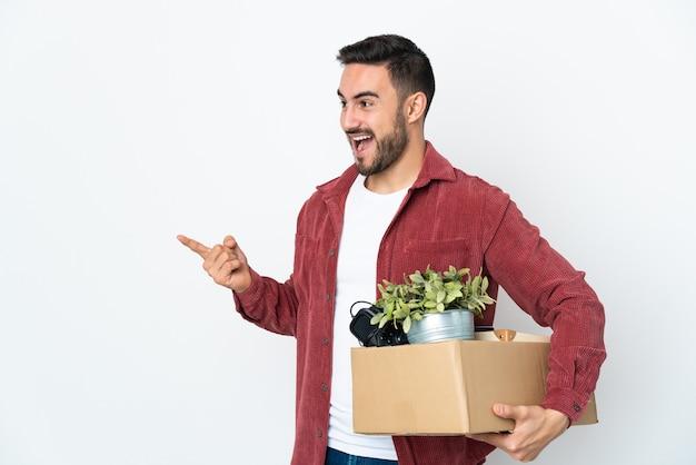 Joven caucásico haciendo un movimiento mientras recoge una caja llena de cosas aisladas en la pared blanca apuntando con el dedo hacia un lado y presentando un producto
