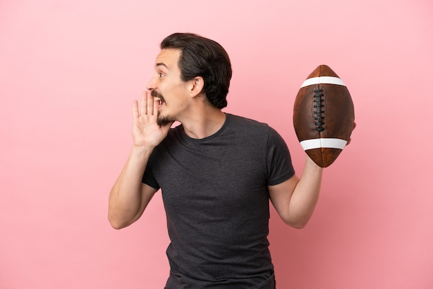 Joven caucásico jugando al rugby aislado sobre fondo rosa gritando con la boca abierta hacia el lado