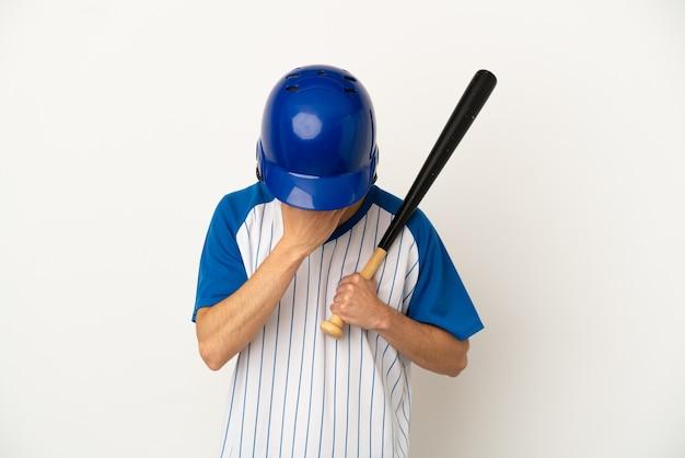 Joven caucásico jugando béisbol aislado sobre fondo blanco con expresión cansada y enferma